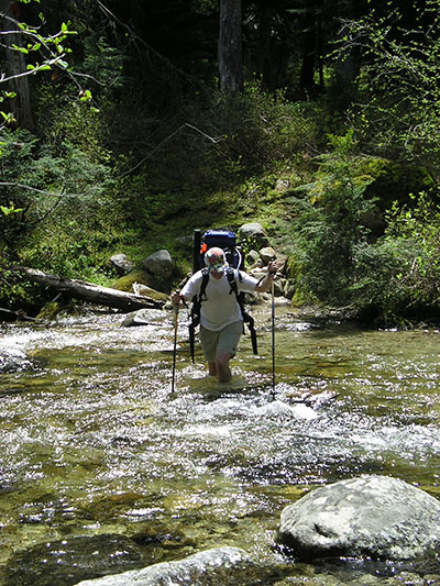 Fording a stream with fishing gear loaded in his backpack, Oppenheimer sets out in the proposed Long Canyon wilderness in the Idaho Panhandle National Forest. PHIL COOK