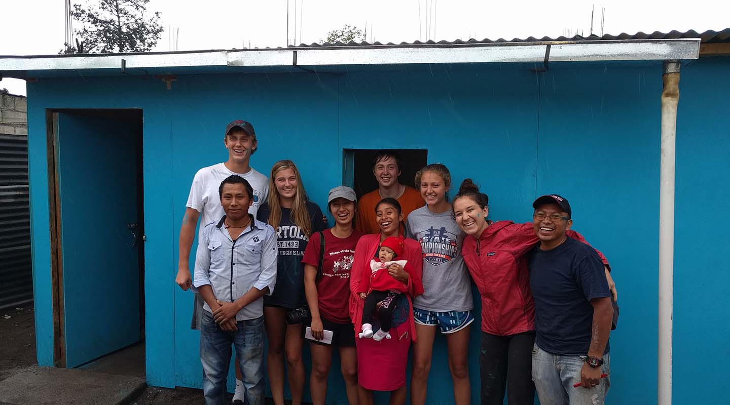 A Guatemalan family at their new home with the Taft team who built it.