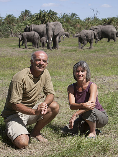 Poole and her husband, Petter Granli, pose with the EB family at the Amboseli Elephant Research Camp, where for many years home was a tent. MARTYN COLBECK, 2008
