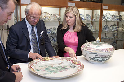 Karina Corrigan '88, curator of Asian export art for the Peabody Essex Museum, shows His Majesty Carl XVI Gustav of Sweden a covered punch bowl with a depiction of the Chinese pavilion at Drottningholm, the estate where the King currently resides. The bowl bears one of only two known images of the pavilion built in 1753 as a birthday gift for Queen Louisa Ulrika of Sweden. The 18th-century porcelain bowl is part of the collection that is not currently on public display, but available to visiting researchers.  PEABODY ESSEX MUSEUM, KATHY TARANTOLA