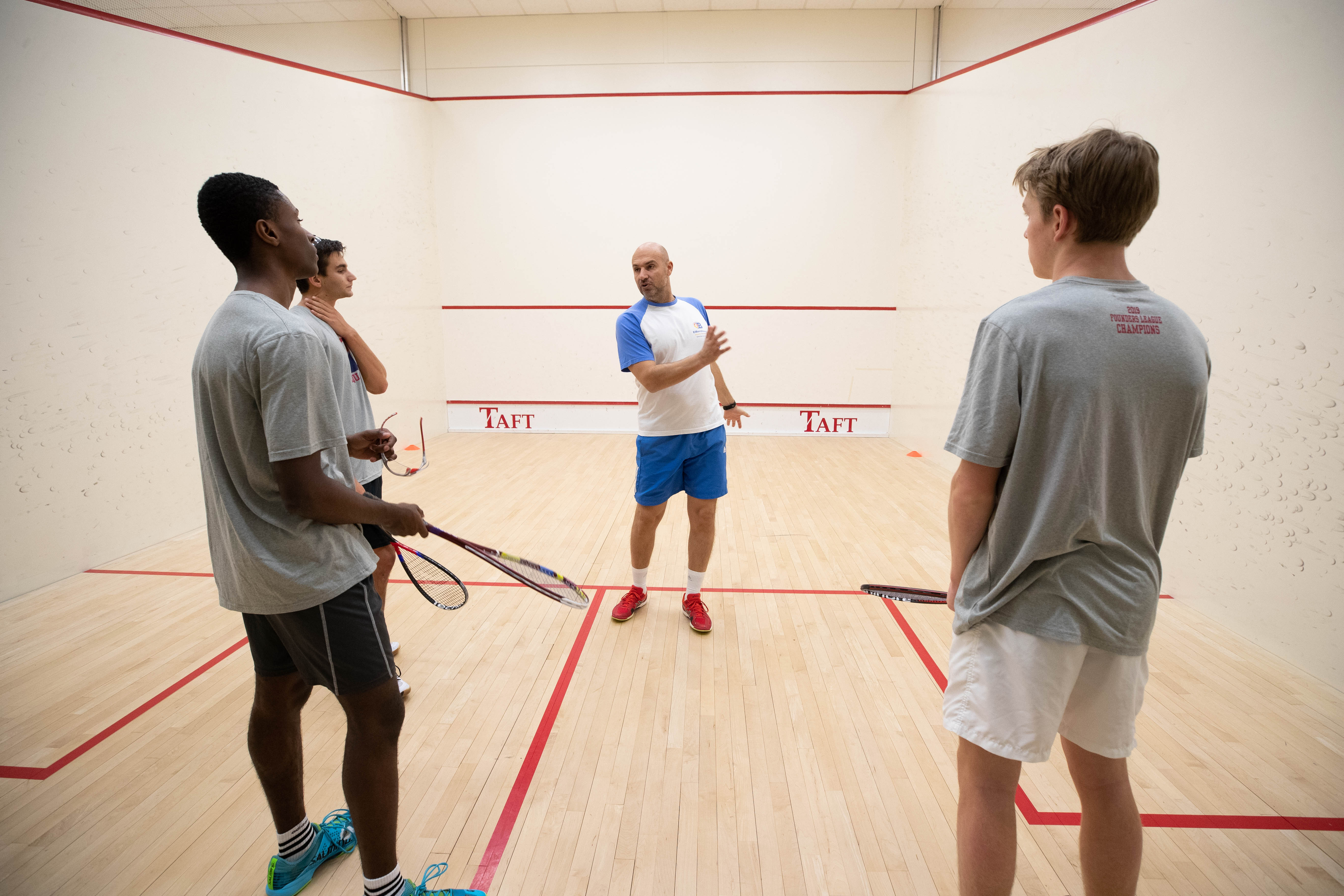 Coach ElBorolossy works with squash players on Taft's court.