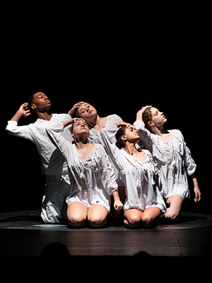 A dance performance during the MLK Day Celebration featuring 5 dancers in white.