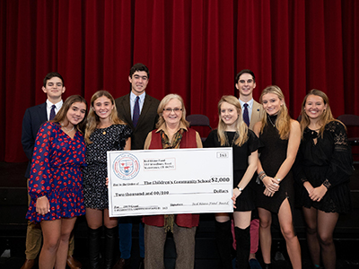 Red Rhino fund members with giant check and awardee