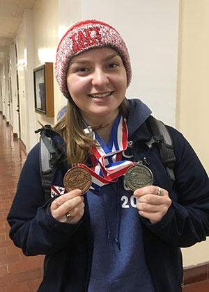 Sydney Gerbel shows her medals from Chemistry Lab and Rocks and Minerals