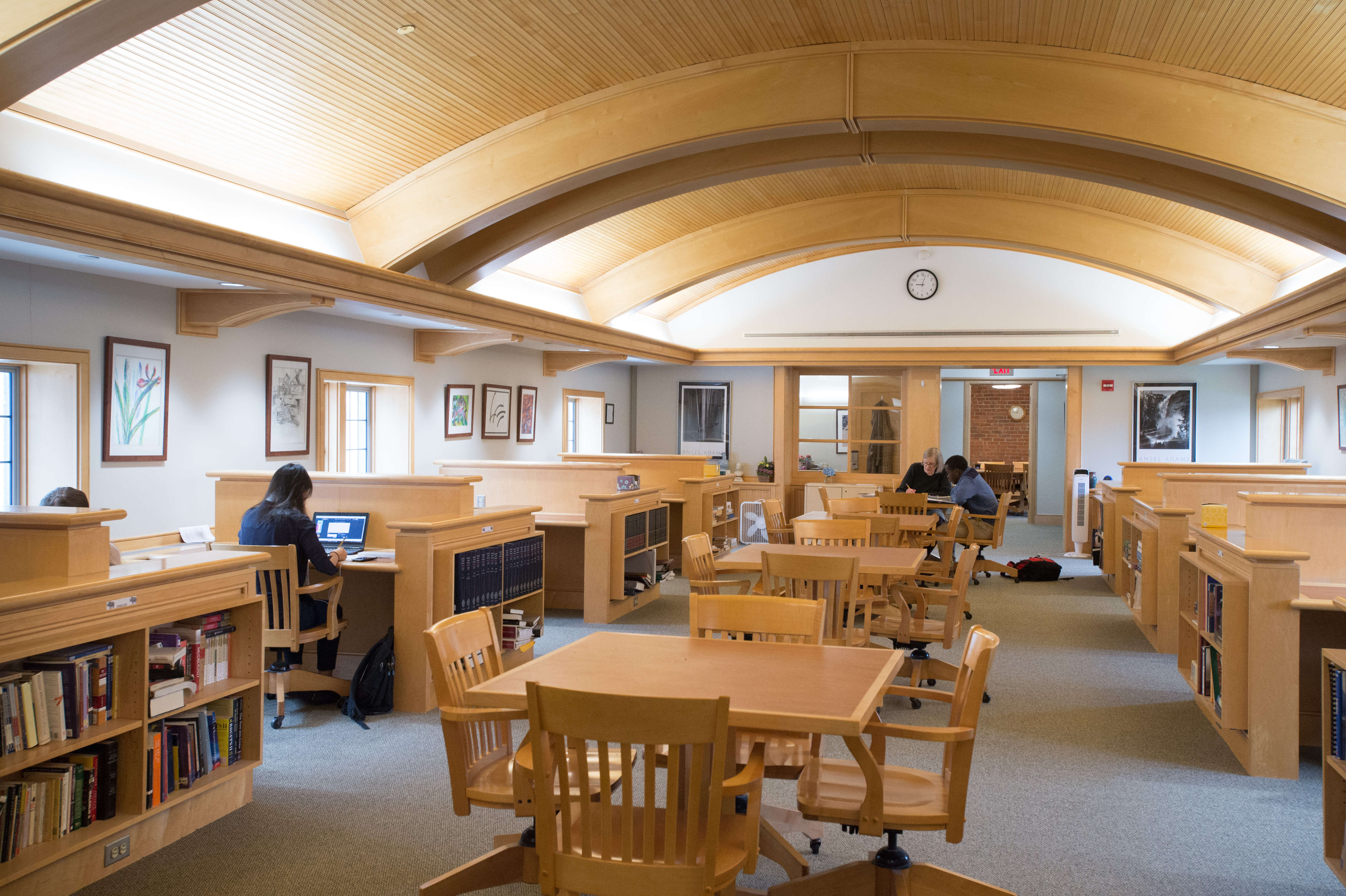 The MAC, a large room with tables and carrels for group and independent work , Teacher with student in background