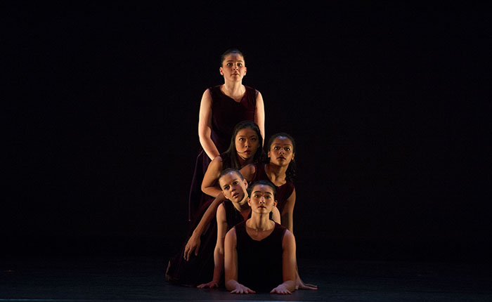 Five students together during a dance performance