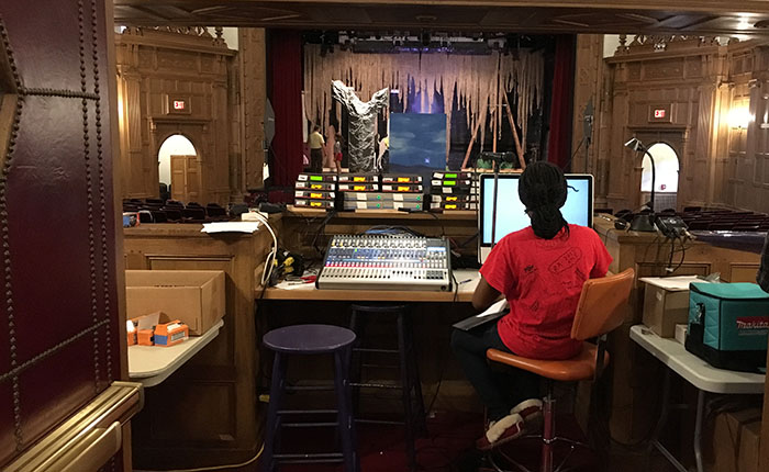A student performing stagecraft work at a computer and sound board
