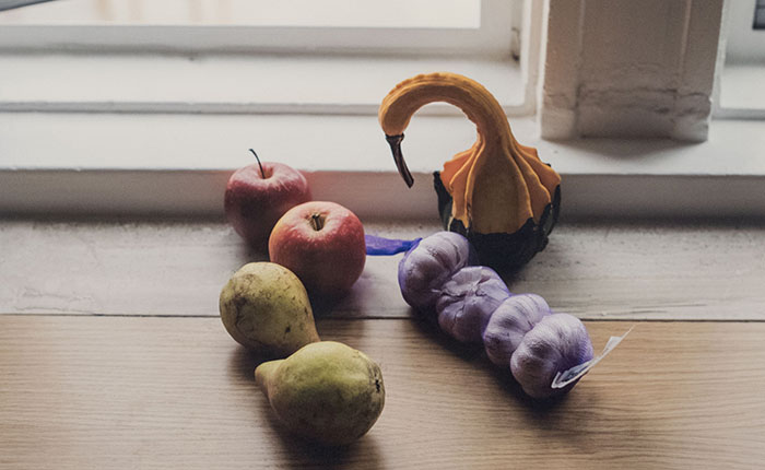 Still life photo of apples, pears, garlic bulbs, and gourd